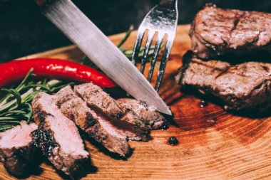 close-up view of sliced grilled meat with rosemary and chili pepper with fork and knife on wooden board