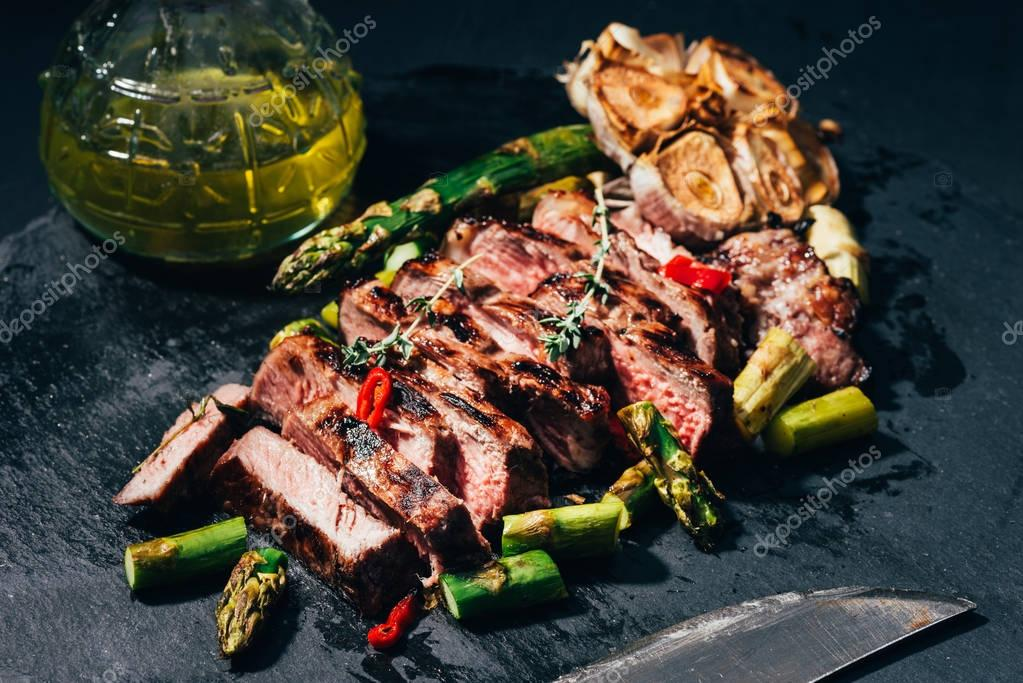 close-up view of tasty sliced grilled meat with asparagus, oil and spices on black
