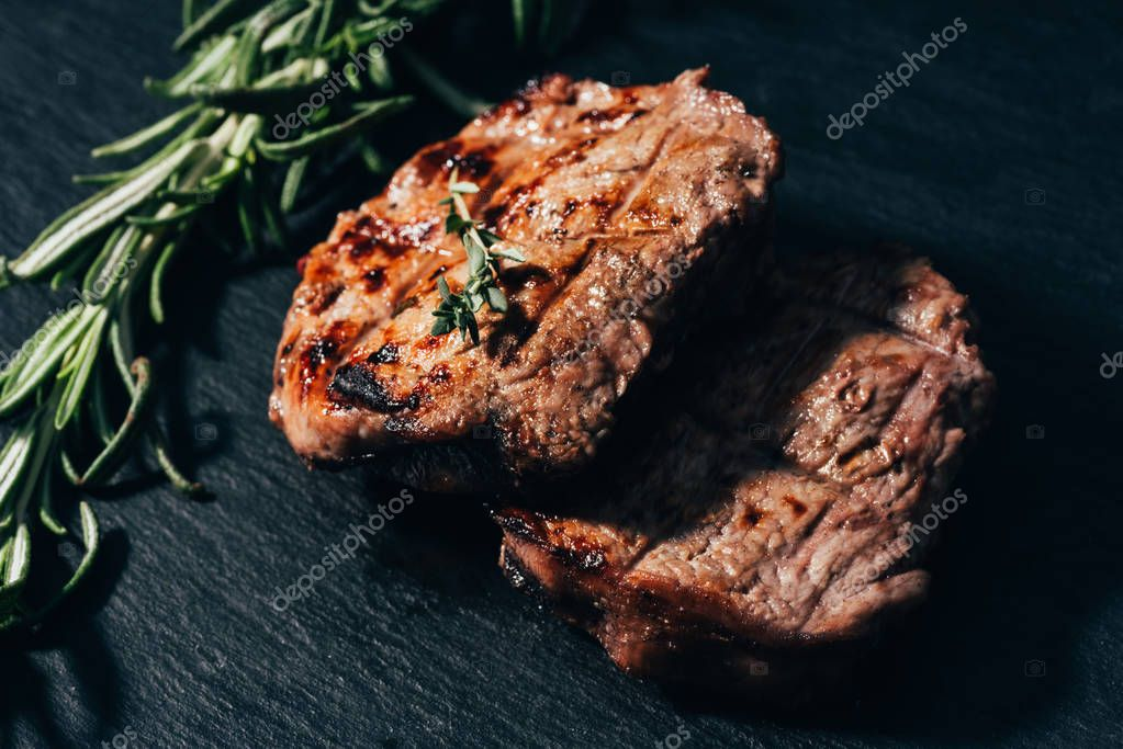 close-up view of delicious grilled steaks with rosemary on black
