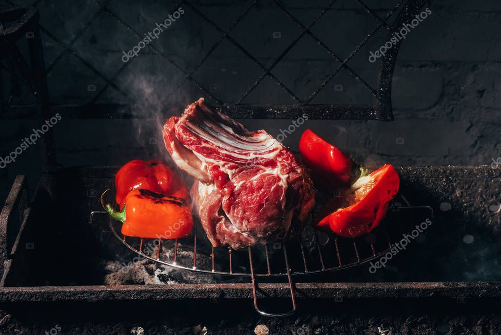 close-up view of delicious raw meat with ribs and peppers preparing on grill