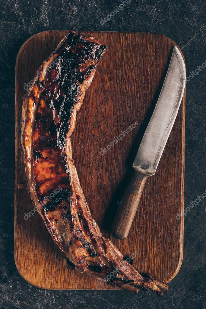 top view of delicious grilled meat with knife on wooden cutting board on black
