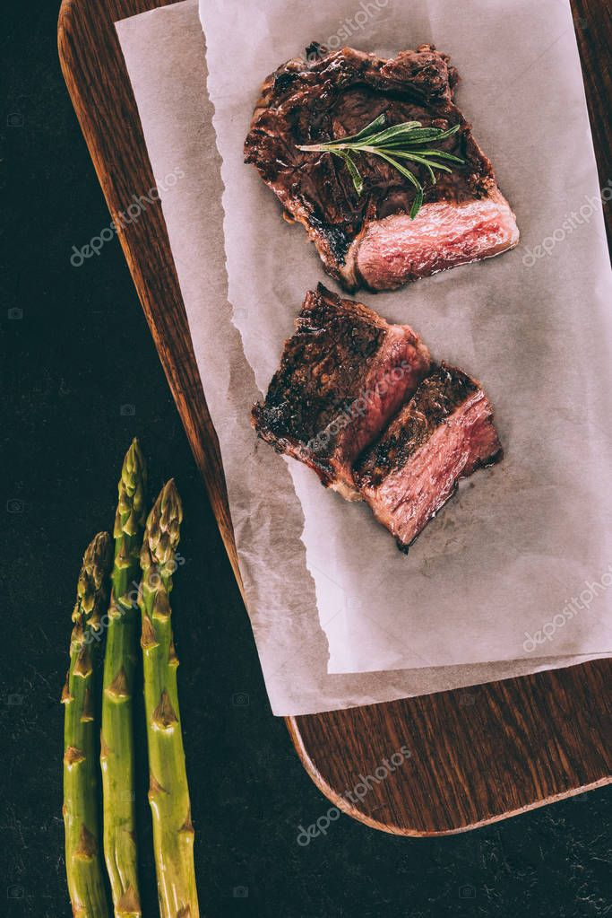 top view of delicious grilled meat on baking paper and asparagus on black
