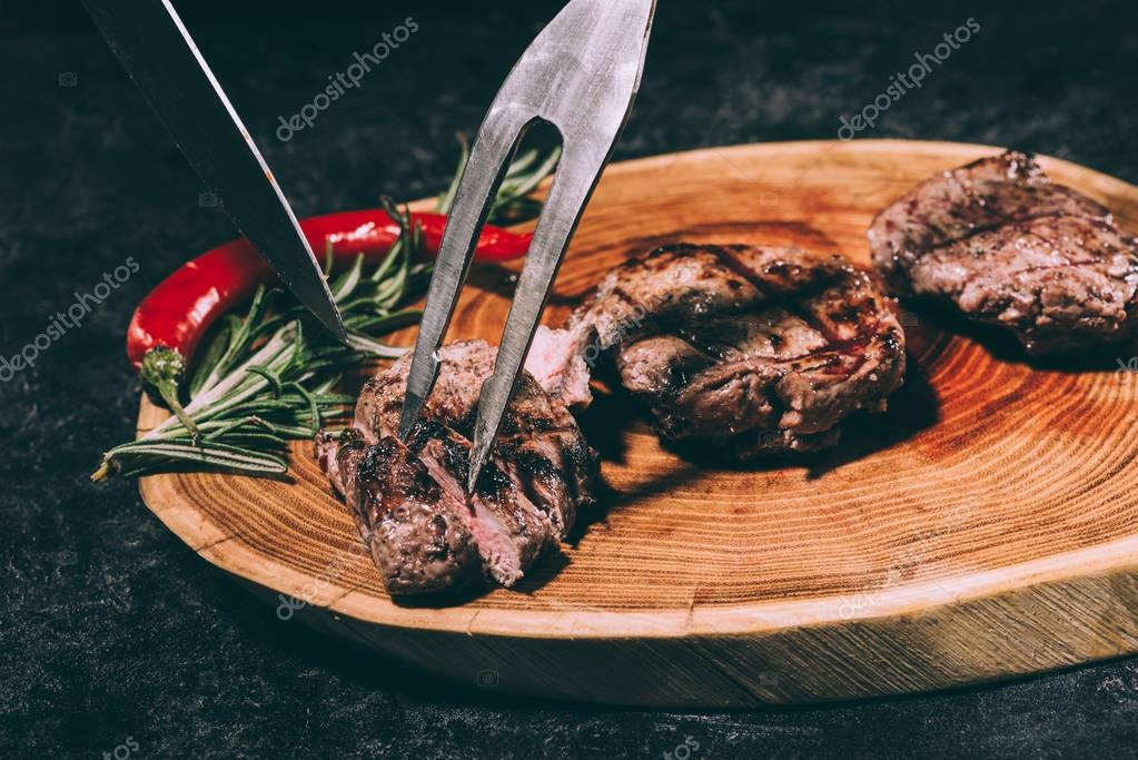 close-up view of meat fork and knife, delicious grilled steaks with rosemary and chili pepper on wooden board