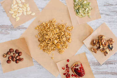 top view of crunchy granola ingredients on baking parchment pieces