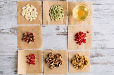 top view of granola ingredients on baking parchment pieces