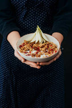 cropped image of female cook holding bowl with homemade granola