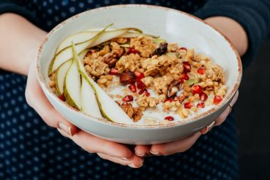 cropped image of female cook holding bowl with granola with fruits and nuts