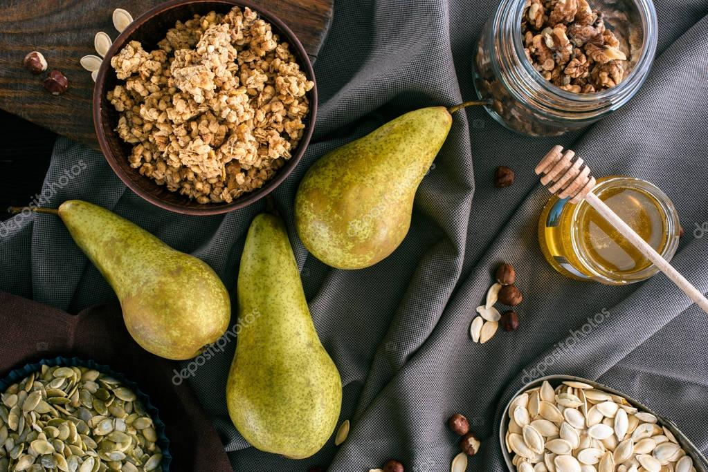 top view of pears, honey and homemade granola on table