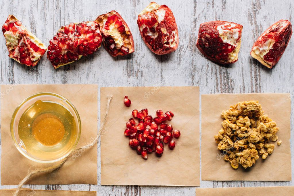 top view of pomegranates and honey for granola preparing on table