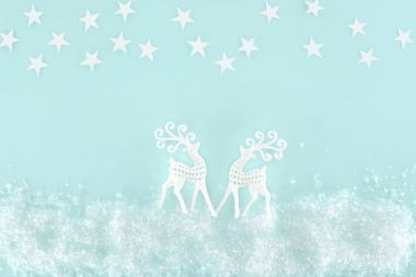 christmas background with decorative snow, stars and paper deer, isolated on light blue