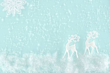 Christmas background with decorative snow, snowflake and paper deer, isolated on light blue stock vector