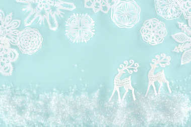Christmas background with decorative snow, snowflakes and paper deer, isolated on light blue stock vector