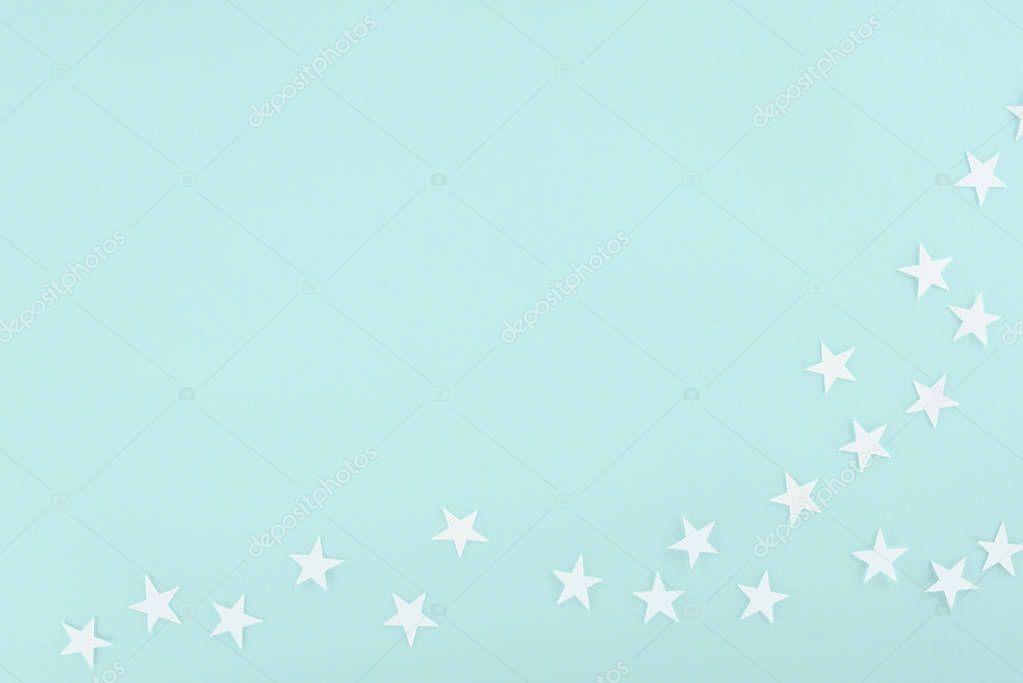 background with white paper stars, isolated on light blue