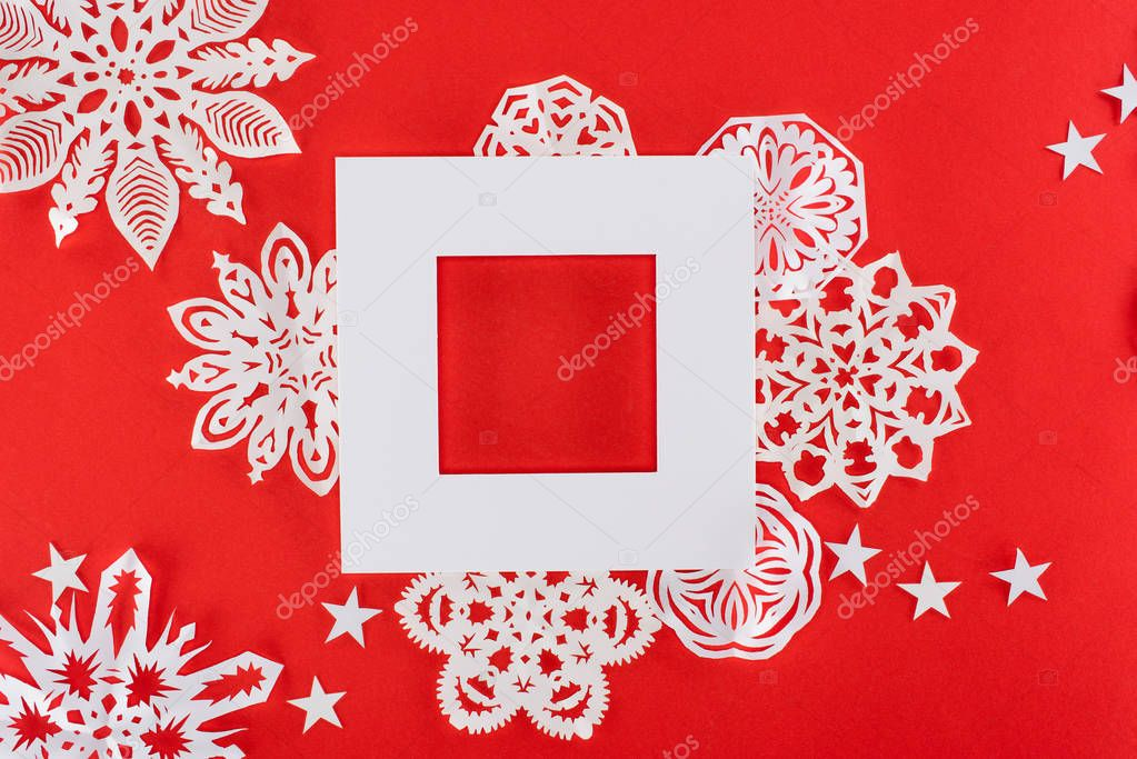 white christmas frame with stars and paper snowflakes around, isolated on red