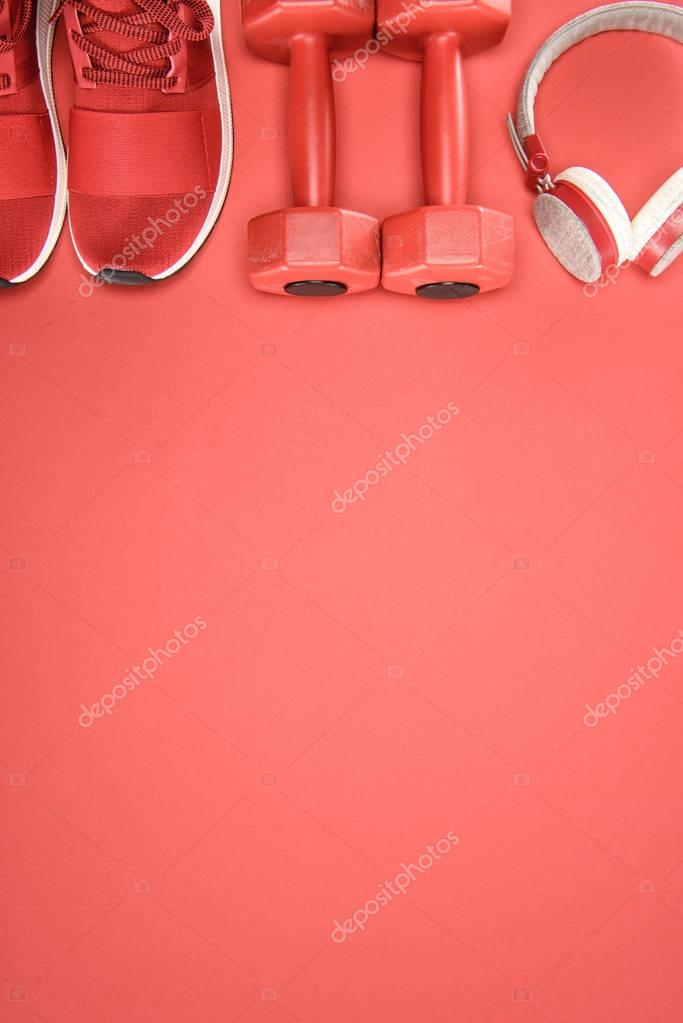 Sports equipment with shoes, dumbbells and headphones isolated on red