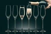oříznutý obraz ženy vylévání šampaňského z láhve do šesti průhledných sklenic na černém pozadí