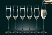 vylévání šampaňského z láhve do šesti průhledných sklenic na černém pozadí