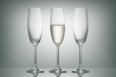 Two empty glasses and one glass with champagne on white stock vector