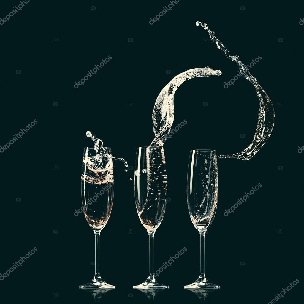 three glasses with splashes of champagne on black