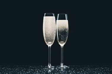 two glasses with champagne with drops on table on black