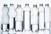 Kunststoffflaschen mit Wasser in Reihe isoliert auf weiß