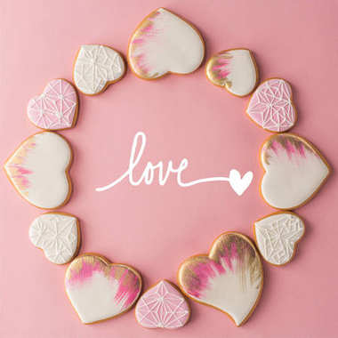 flat lay with arrangement of glazed heart shaped cookies isolated on pink surface