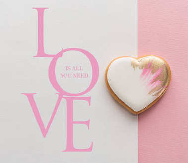 Top view of glazed heart shaped cookie on pink surface stock vector