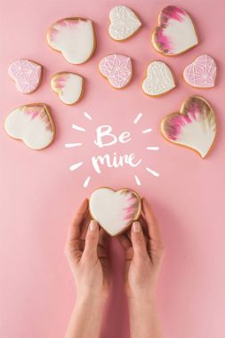 Partial view of woman holding glazed cookie in hands isolated on pink, st valentines day concept stock vector