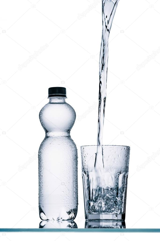 plastic bottle and water pouring into glass isolated on white