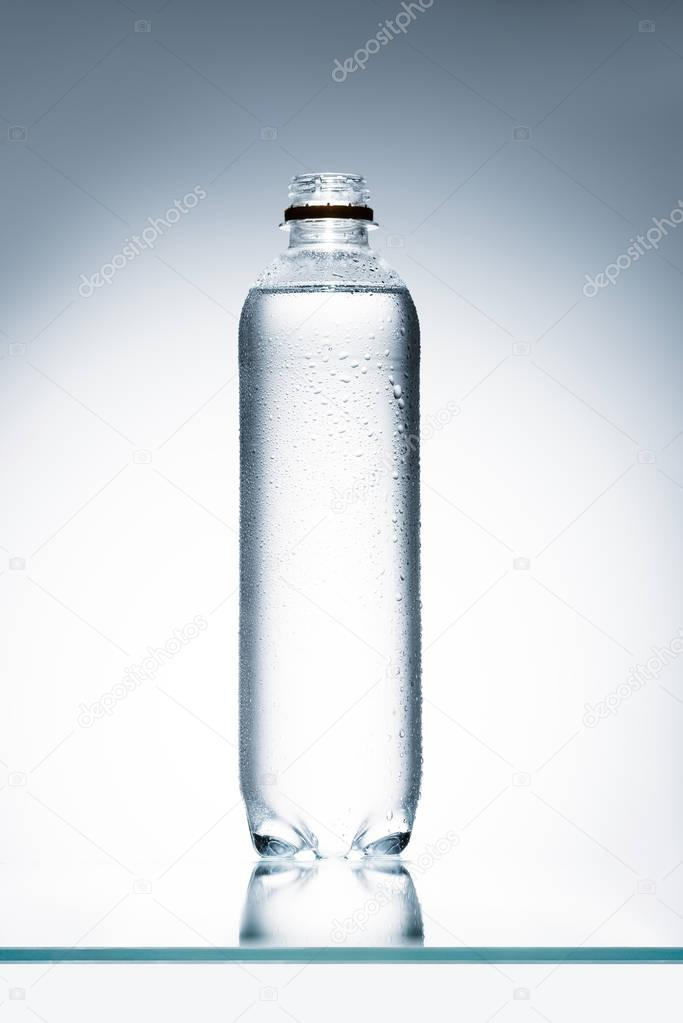 plastic bottle full of water on reflective surface