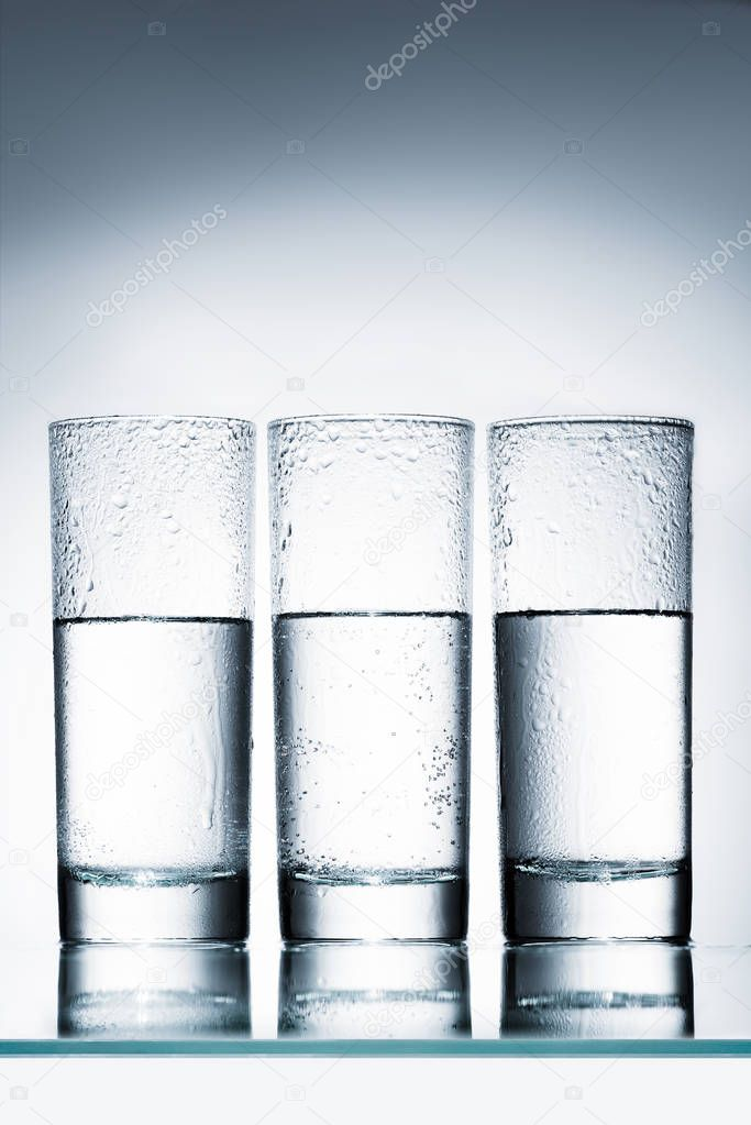 half full glasses of water in row on reflective surface