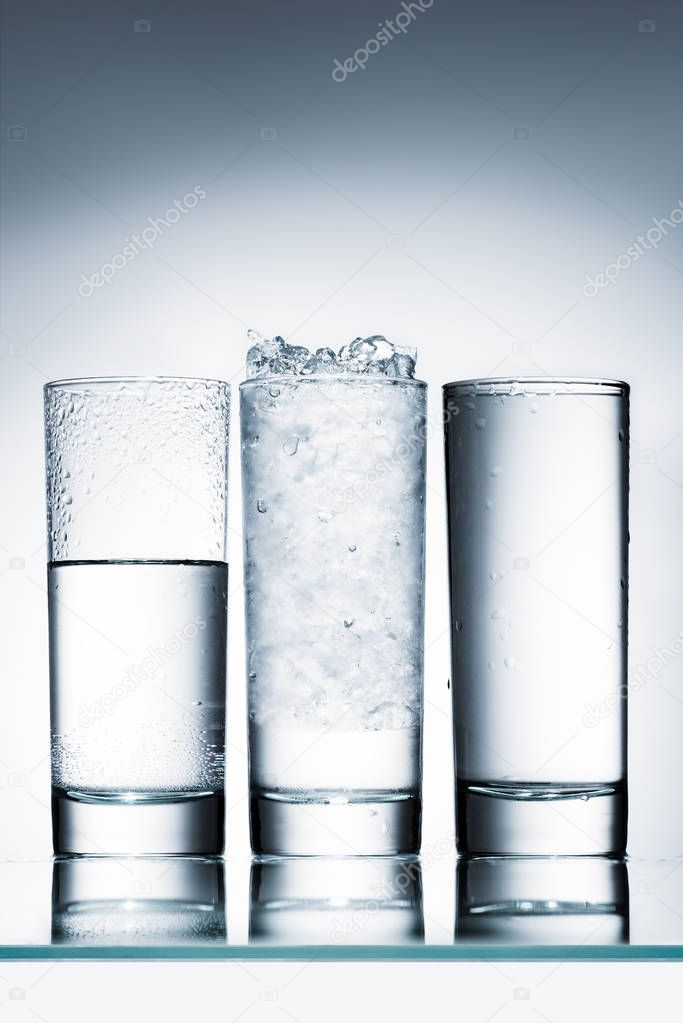 glasses of water in row and one with ice on reflective surface