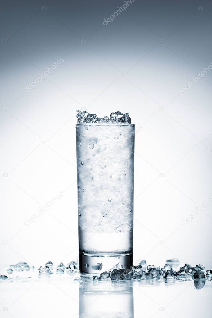 glass of cold water with crushed ice on reflective surface on white