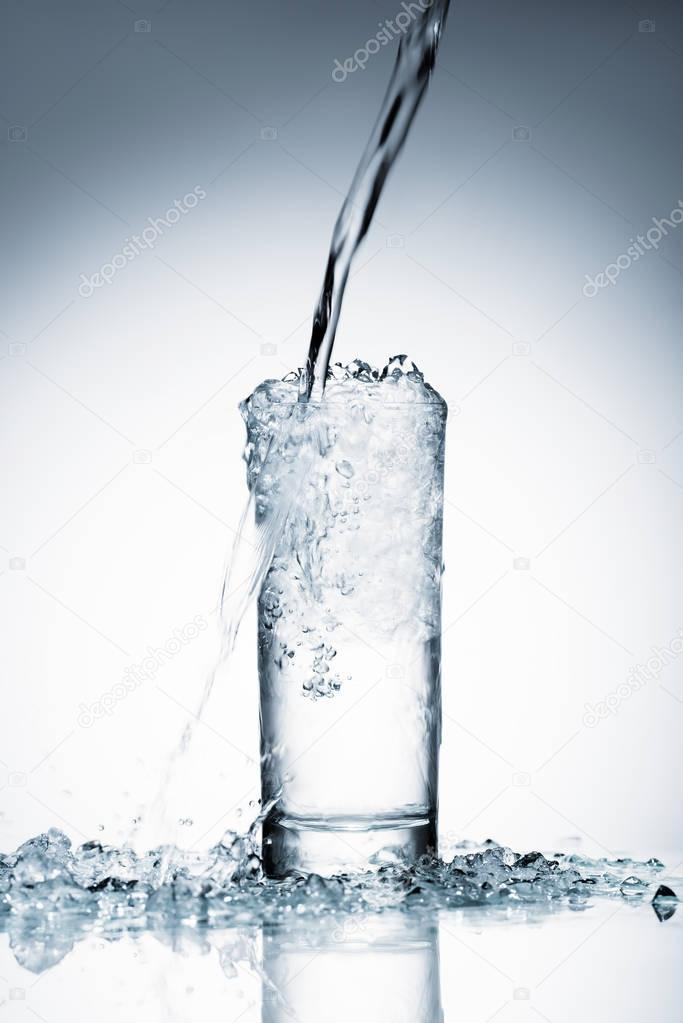close-up shot of water pouring into glass on white