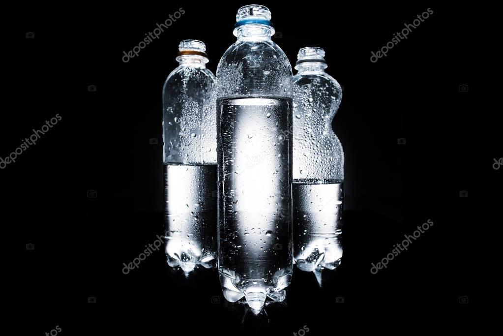 various plastic bottles of water on dark