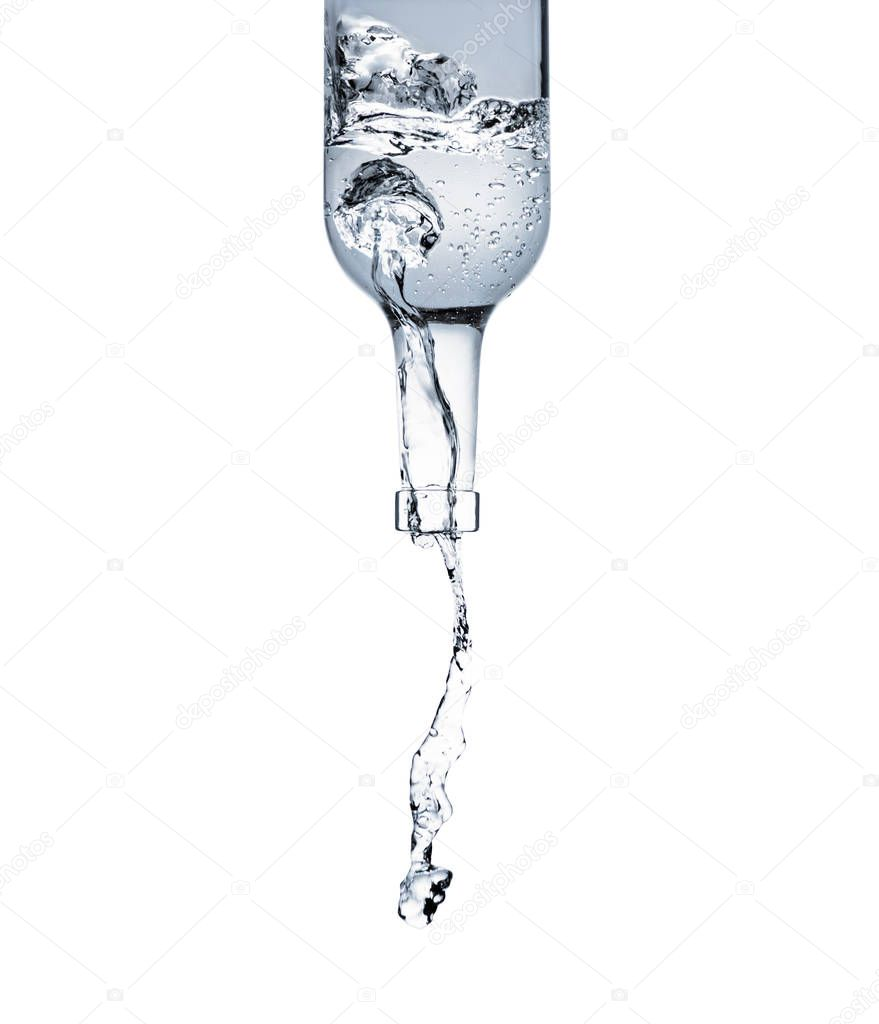 motion shot of water pouring from glass bottle isolated on white