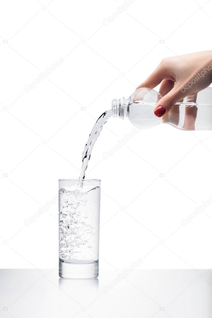 cropped shot of woman pouring clean water into glass from plastic bottle isolated on white