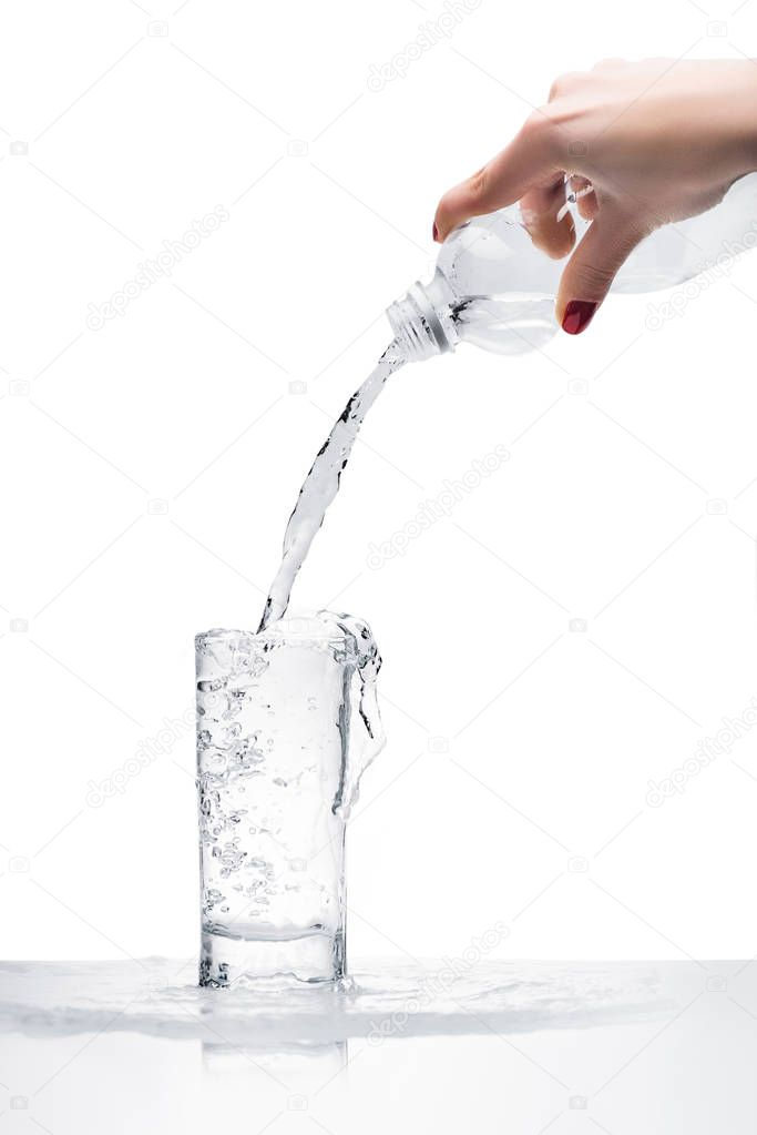 cropped shot of woman pouring water into glass from plastic bottle isolated on white
