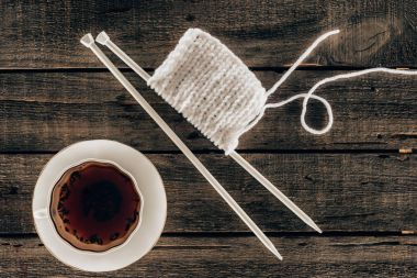 top view of knitting needles with yarn and cup of tea on wooden background