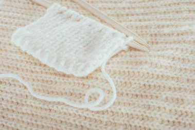 close up of knitting needles with white woolen yarn