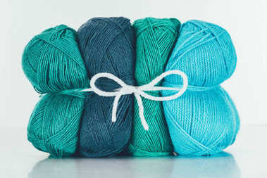 blue and green knitting yarn balls on white