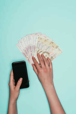 cropped shot of woman with cash and smartphone isolated on turquoise