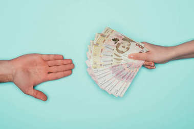 cropped shot of people passing cash isolated on turquoise