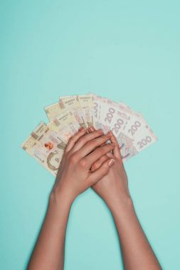 cropped shot of woman with bunch of cash isolated on turquoise