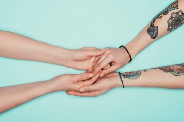 cropped shot of sensual women holding hands of each other isolated on turquoise