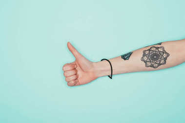 cropped shot of woman showing thumb up isolated on turquoise