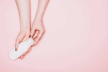 cropped shot of with bottle of lotion isolated on pink