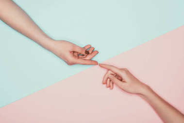 cropped shot of women touching fingers on halved pink and turquoise surface