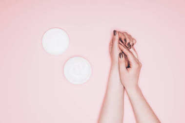 cropped shot of woman applying hand cream isolated on pink