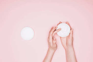 cropped shot of woman taking moisturizing cream from can isolated on pink